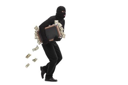 Studio shot van een mannelijke inbreker met een masker op zijn hoofd lopen met een koffer vol geld op een witte achtergrond