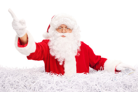 shredded paper: Angry Santa Claus pointing with his finger and standing in a pile of shredded paper isolated on white background