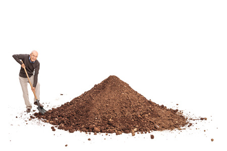 dirt background: Cheerful senior shoveling a big pile of dirt and looking at the camera isolated on white background