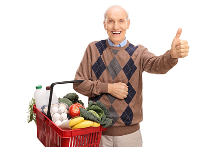 posing  agree: Senior holding a shopping basket full of groceries and giving a thumb up isolated on white background Stock Photo