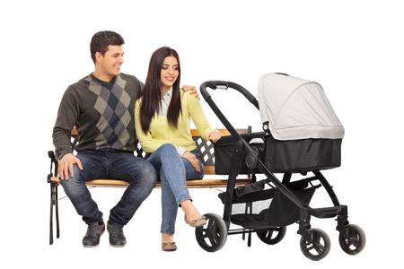 bebe sentado: Studio foto de una joven padres sentados en un banco de madera con un cochecito de bebé al lado de ellos aislado en el fondo blanco