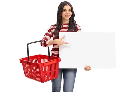 Fröhliche junge Frau mit einem leeren Warenkorb und zeigte auf eine leere Banner auf weißem Hintergrund
