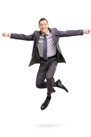 midair: Full length vertical shot of a joyful businessman jumping out of happiness shot in mid-air isolated on white background