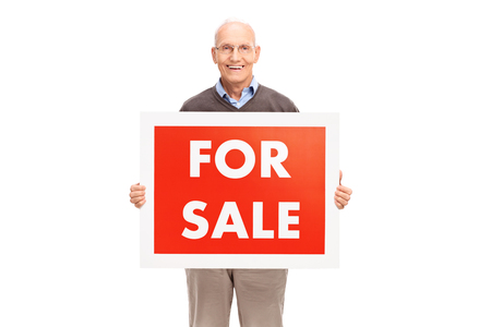for sale sign: Studio shot of a senior gentleman holding a for sale sign and looking at the camera isolated on white background