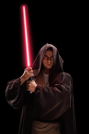 黒の背景に赤いレーザー剣を持つ戦士が男性の垂直ショット
