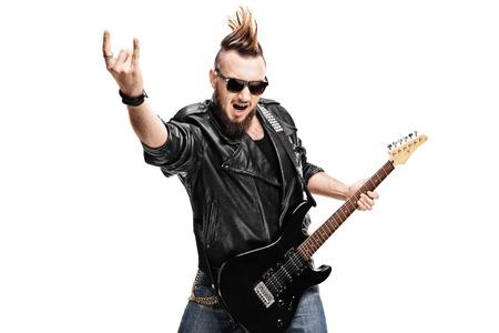 El estudio tiró de un guitarrista de punk rock que toca la guitarra y el gesto de la roca aislada en el fondo blanco haciendo Foto de archivo