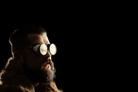 indie: Studio shot of a young man with beard and a black goggles on black background Stock Photo