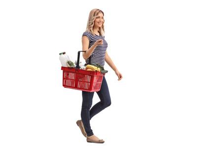 歩いていると、白い背景で隔離の食料品買い物かごを運ぶ若い女性の完全な長さの肖像画