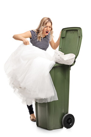 trash the dress: Vertical shot of an angry young woman throwing her wedding dress in the trash isolated on white background