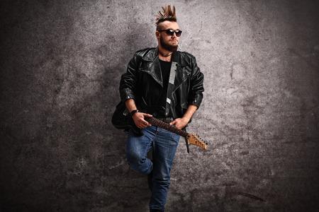 Joven punk sosteniendo una guitarra eléctrica y apoyado contra un muro de hormigón