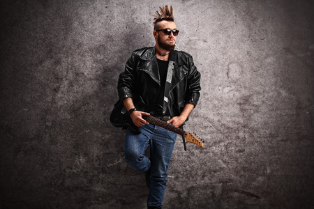 Young punk rocker holding an electric guitar and leaning against a concrete wall