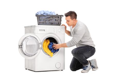 Giovane mettere i vestiti in lavatrice isolato su sfondo bianco