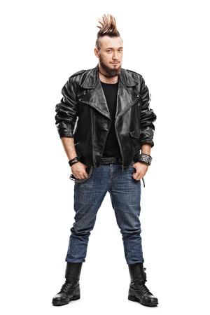 Retrato de cuerpo entero de un punk masculino joven en una chaqueta de cuero negro y botas negras sobre fondo blanco