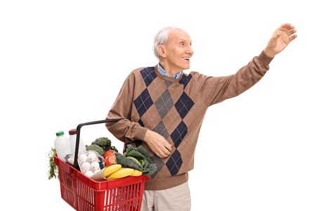 reach customers: Cheerful senior holding a shopping basket and reaching for something isolated on white background Stock Photo
