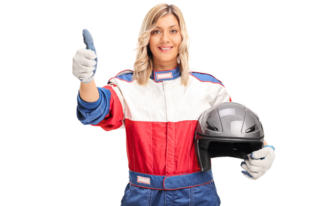 female driver: Studio shot of a young female car racer holding a helmet and giving a thumb up isolated on white background