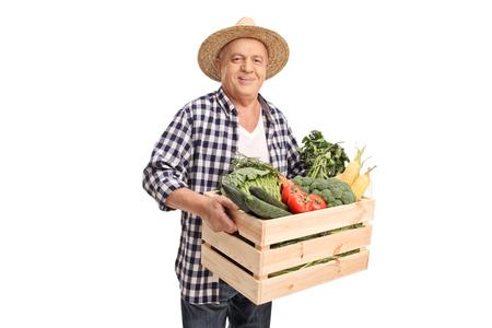 Ltere Landarbeiter eine Holzkiste voll mit frischem Gemüse isoliert auf weißem Hintergrund Standard-Bild - 51993622