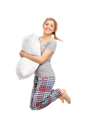 studio  isolated: Vertical profile shot of a blond woman holding a pillow and jumping isolated on white background