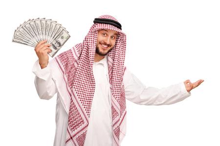 hombre arabe: Joven árabe difusión de una pila de dinero y haciendo un gesto de bienvenida con la mano aisladas sobre fondo blanco