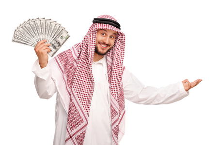 money man: Young Arab spreading a stack of money and making a welcoming gesture with his hand isolated on white background