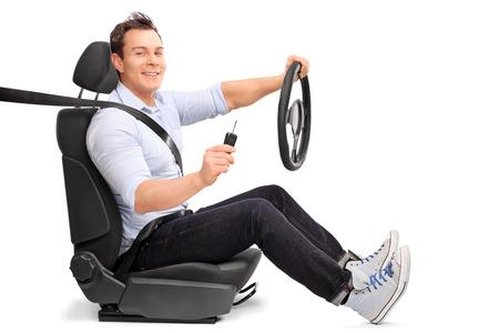 Jonge man zit op een autostoel en houdt een stuurwiel en een autosleutel geïsoleerd op een witte achtergrond