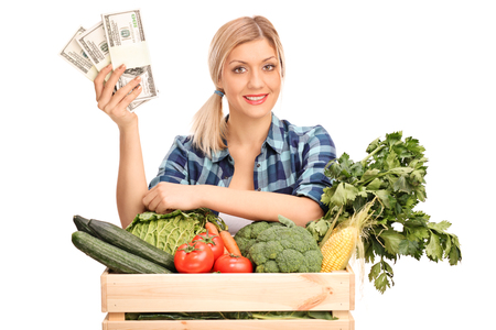cash crop: Young female agricultural worker holding a few stacks of money and standing behind a crate with vegetables isolated on white background
