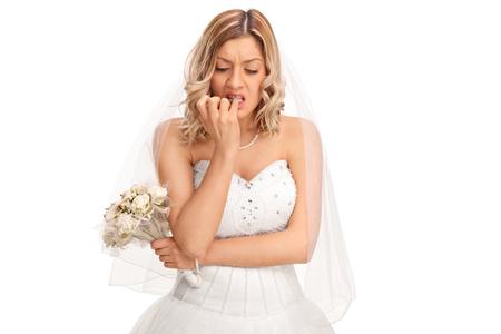 白い背景に分離された彼女の指の爪を噛む白いウェディング ドレスで若い神経質な花嫁