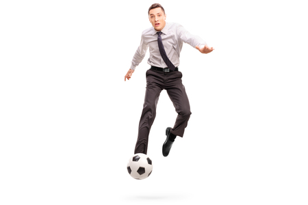 studio shoot: Studio shot of a young businessman kicking a football shot in mid�air isolated on white background