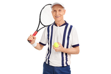 70s tennis: Studio shot of a senior tennis player holding a racquet and a ball isolated on white background
