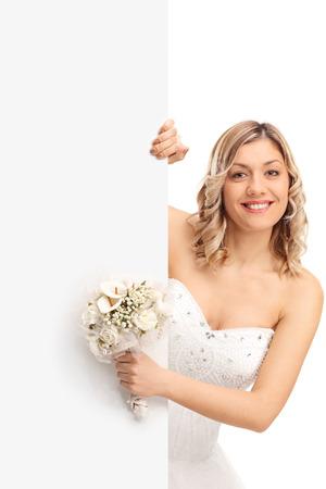 Verticale shot van een jonge bruid die een bruiloft bloem en zich achter een leeg paneel op een witte achtergrond Stockfoto