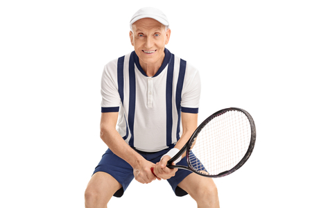 70s tennis: Studio shot of a cheerful senior playing tennis and looking at the camera isolated on white background Stock Photo