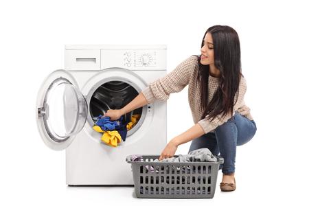 Jonge vrouw legen van een wasmachine op een witte achtergrond Stockfoto