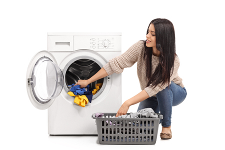 wash machine: Young woman emptying a washing machine isolated on white background