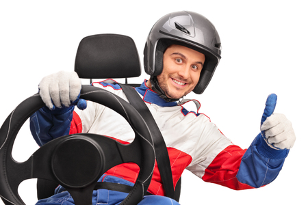Joyful car racer holding a steering wheel and giving a thumb up isolated on white background Stock Photo