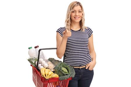 mujer sola: Mujer rubia joven que lleva una cesta llena de comestibles aislados en fondo blanco