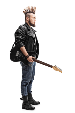 male fashion: Full length profile shot of a young punk rocker holding an electric guitar isolated on white background