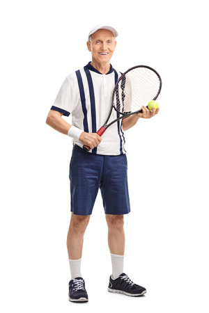 70s tennis: Full length portrait of a senior man holding a racket and a tennis ball isolated on white background