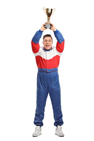 trofeo: Retrato de cuerpo entero de un campeón de carreras de coches que sostiene un trofeo de oro sobre su cabeza aislada en el fondo blanco Foto de archivo