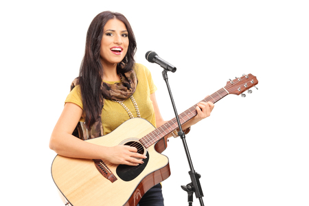 signer: Female signer playing on acoustic guitar and singing on a microphone isolated on white background Stock Photo