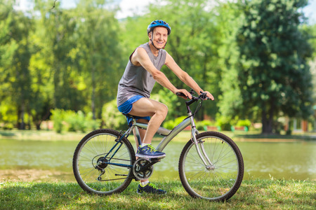 Active senior man riding a bike in park on a beautiful summer day shot with tilt and shift lens Stock Photo
