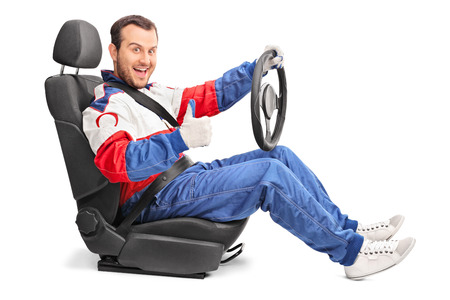 posing  agree: Joyful car racer sitting in a car seat and giving a thumb up isolated on white background