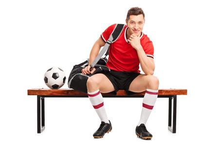 Junger Fußballspieler auf einer Holzbank und schaut in die Kamera sitzt isoliert auf weißem Hintergrund