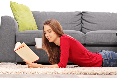 girl lying studio: Young relaxed woman lying on the floor and reading a book in front of a gray sofa isolated on white background