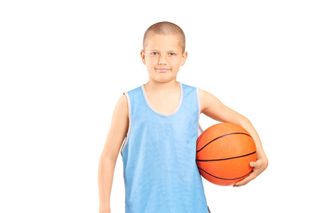 boy ball: Little boy in a blue jersey holding a basketball and looking at the camera isolated on white background