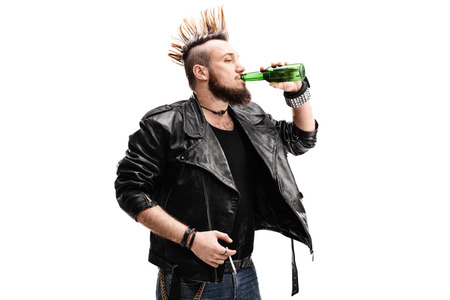delinquent: Studio shot of a young male punk rocker holding a cigarette and drinking a beer isolated on white background