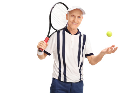 70s tennis: Senior tennis layer holding a racket and throwing the ball isolated on white background