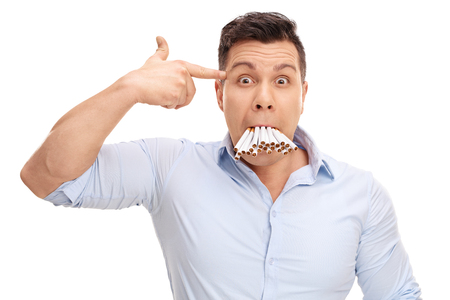 holding gun to head: Studio shot of a man with a bunch of cigarettes in his mouth holding a hand gun against his head isolated on white background