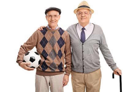 pelota de futbol: Studio foto de un señor mayor que sostiene un balón de fútbol y posando con un viejo amigo aislado en el fondo blanco Foto de archivo
