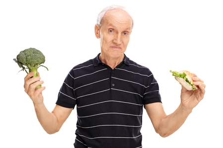 indecisive: Indecisive senior man holding a piece of broccoli in one hand and a sandwich in the other isolated on white background