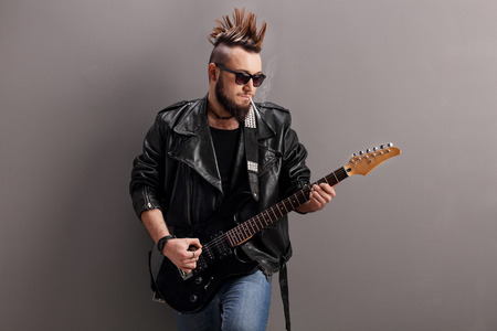 rocker: Young punk rocker smoking a cigarette and playing electric guitar against a gray wall Stock Photo