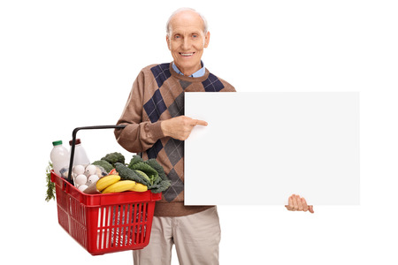 shopper: Cheerful senior holding a shopping basket full of groceries and a blank white signboard isolated on white background